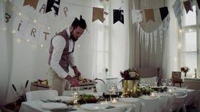 Młody człowiek z łękiem i kamizelka ustawia stół dla salowego przyjęcia zbiory wideo