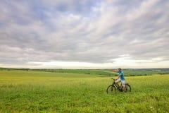 Młody człowiek z bicyklem na zieleni polu na pogodnym letnim dniu Zdjęcie Stock