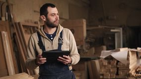 Młody człowiek z brodą chodzi wokoło ciesielka sklepu z pastylką w jego rękach Patrzeje z powrotem, ocenia, zdjęcie wideo
