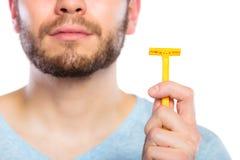 Młody człowiek z brodą pokazuje żyletki ostrze obrazy royalty free