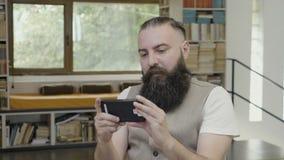 Młody człowiek z brody czytaniem coś na jego smartphone i mieć no! no! reakcję - zbiory