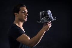 Młody człowiek z ciemnym koszulki mienia kapeluszem Obrazy Stock