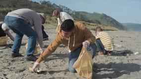 Młody człowiek z kciukiem czyści plażę zbiory wideo