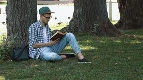 Młody człowiek z książką w parku zdjęcie wideo