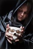 Młody człowiek z ludzką czaszką w ręce Zdjęcie Royalty Free