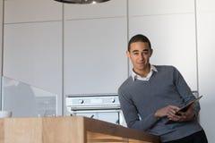 Młody człowiek z pastylką w kuchni Fotografia Stock