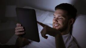 Młody człowiek z pastylka komputerem osobistym w łóżko sypialni w domu zdjęcie wideo