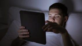 Młody człowiek z pastylka komputerem osobistym w łóżko sypialni w domu zbiory