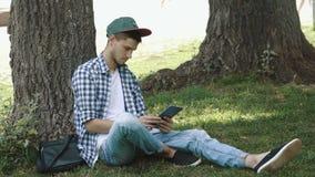 Młody człowiek z pastylka komputerem w parku zdjęcie wideo
