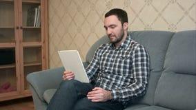 Młody człowiek z pastylka komputeru osobistego komputerem ma wideo wezwanie w domu zbiory