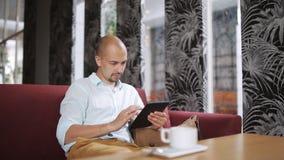 Młody człowiek z pastylki komputerową pije kawą w kawiarni zbiory