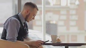 Młody człowiek z pastylki komputerową pije kawą wewnątrz zdjęcie wideo