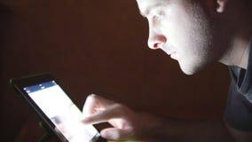 Młody człowiek z pastylki komputerowym lying on the beach na kanapie Facet używa pastylka komputer nocnego w domu Rozjarzony świa zdjęcie wideo