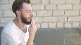 Młody człowiek z piękną brodą w białym podkoszulku bez rękawów przeciw szaremu ściana z cegieł z papierosem zdjęcie wideo