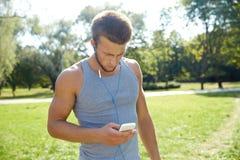 Młody człowiek z słuchawkami i smartphone przy parkiem Zdjęcia Royalty Free