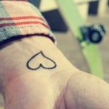 Młody człowiek z sercem tatuującym w jego nadgarstku Obrazy Stock