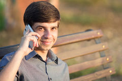 Młody człowiek z smartphone na ławce Zdjęcia Royalty Free