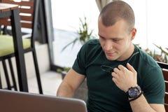 Młody człowiek z szkieł spojrzeniami przy laptopem i surfuje internet zdjęcie royalty free