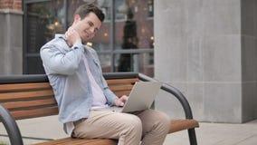 Młody człowiek z szyja bólem używać laptop plenerowego zbiory wideo
