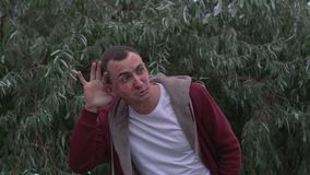 Młody człowiek z twarzą pomadek oceny buziaki pełno jest stawia jego ręki ucho i słuchanie zbiory wideo