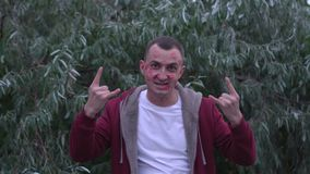 Młody człowiek z twarzą pomadek oceny buziaki pełno robi chłodno rockowemu gestowi zdjęcie wideo