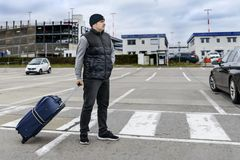 Młody człowiek z walizki stojakami na drodze przed lotniskowym budynkiem: zdjęcie royalty free