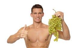 Młody człowiek z winogronami Zdjęcia Royalty Free