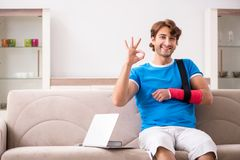 Młody człowiek z zdradzonym ręki obsiadaniem na kanapie fotografia royalty free