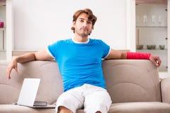 Młody człowiek z zdradzonym ręki obsiadaniem na kanapie obraz stock