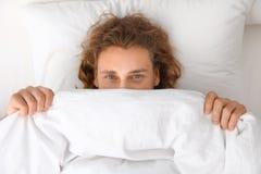 Młody człowiek zakrywa jego twarz z koc podczas gdy kłamający na poduszce bedtime obrazy royalty free