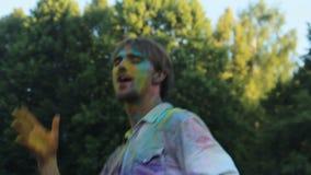 Młody człowiek zakrywający w barwionym farba tanu i ma zabawę przy Holi festiwalem zbiory wideo