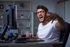 Młody człowiek zostaje póżno w biurze robić nadgodzinowej pracie Fotografia Stock
