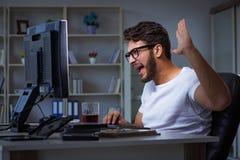 Młody człowiek zostaje póżno w biurze robić nadgodzinowej pracie Zdjęcia Royalty Free