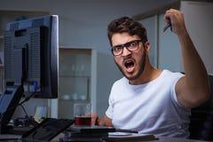 Młody człowiek zostaje póżno w biurze robić nadgodzinowej pracie Obrazy Royalty Free