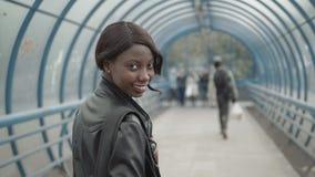 Młody czarny żeński nauczyciel jest ubranym małą skórzanej kurtki teczkę z afro fryzurą, chodzącą od budynku biurowego out Fotografia Royalty Free