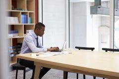 Młody czarny biznesmen pracuje samotnie w biurze zdjęcie stock