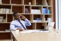 Młody czarny biznesmen używa smartphone w sala posiedzeń obraz royalty free