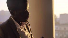 Młody czarny biznesmen w kostium rozmowie na telefon pozyci okno w biurze na zmierzchu zbiory wideo