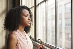 Młody czarny bizneswoman patrzeje z okno obraz royalty free