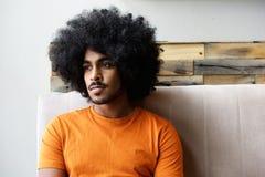 Młody czarny facet myśleć z afro obsiadaniem w domu Obraz Royalty Free