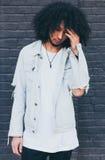 Młody czarny modny mężczyzna z afro włosy pozuje na grafitu tle _ Ubierający w cajg kurtce, czarnej Zdjęcia Royalty Free