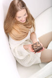 Młody długowłosy blondynki obsiadanie na kanapie z teraźniejszym pudełkiem Zdjęcia Royalty Free