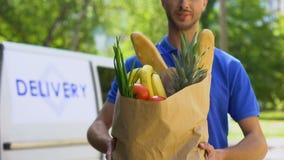 Młody deliveryman pokazuje sklep spożywczy torbę, sklep usługa, online rozkazu transport zbiory