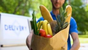 Młody deliveryman pokazuje sklep spożywczy torbę, sklep usługa, online rozkazu transport zdjęcia stock