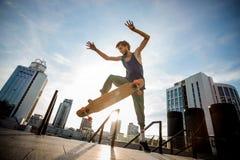Młody deskorolkarz skacze na pokładzie miasto budynków przeciw fotografia stock