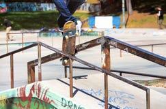 Młody deskorolkarza doskakiwanie na poręczu w skatepark Obraz Royalty Free