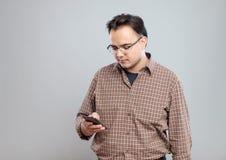 Młody dorosły mężczyzna używa telefon komórkowego fotografia royalty free