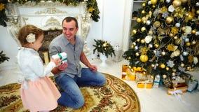Młody Dorosły tata Z Małymi córki wymiany prezentami i Ściskać Each Inny w Wielkim pokoju na tle Dekorujący zdjęcie wideo