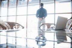 Młody dyrektor wykonawczy i lider stoi pewnie, w najwyższego piętra biurze, patrzeje miasto below Zdjęcia Stock