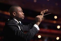 Młody dyrygent z batutą podnoszącą przy występem zdjęcia royalty free